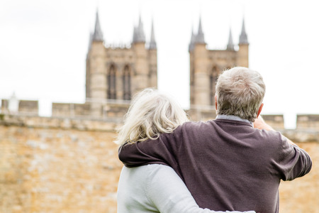 A elderly couple exploring in their retirement, pointing and looking at Loncoln cathedral in the distance