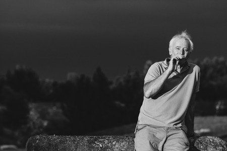 A handsome older man puffing on an e-cigarette in black and white