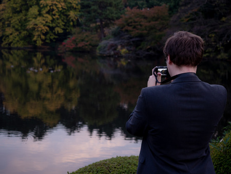 A man taking pictures of a scenic lake in a park