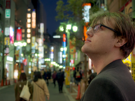 A young man exploring the neon lights of a big Asian city