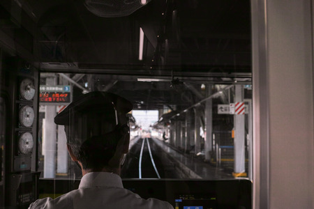 Rear view of a train driver pulling into a station