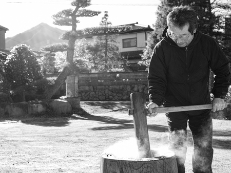 An older man making mochi in the winter with steaming hot rice. Reklamní fotografie