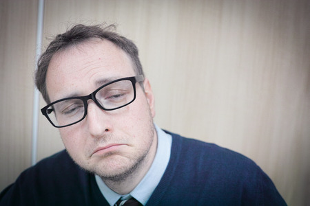 A man in glasses looking very glum at work