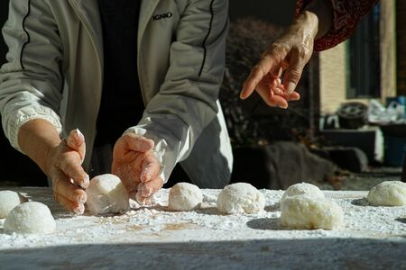 An older woman shaping mochi balls ready for the new year