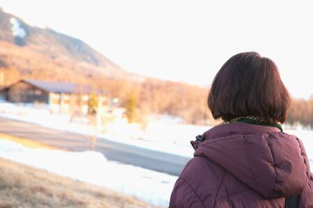 The back of a womans head as she observes Winter scenery