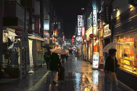 Tokyo, Japan - 11/6/2018: People walking down a wet street in Koenji at night Archivio Fotografico - 132422212