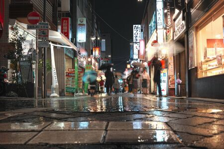 Tokyo, Japan - 11/6/2018: People walking down a wet street in Koenji at night Archivio Fotografico - 132422213