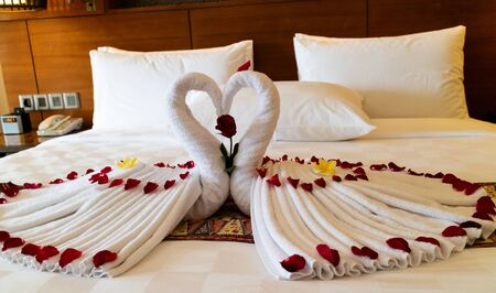 Origami swans made out of towels and laid out on a bed in a honeymoon suite in a luxury hotel Stock Photo - 130810793