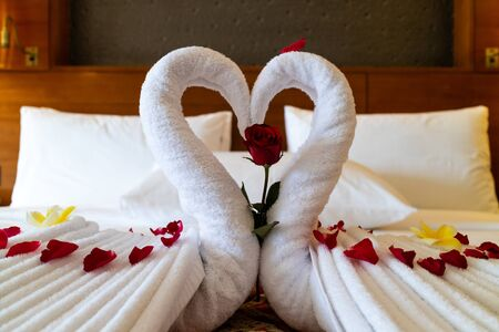 Origami swans made out of towels and laid out on a bed in a honeymoon suite in a luxury hotel Stock Photo - 130810796