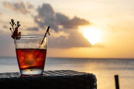 An iced summer cocktail isolated in front of a sunset over the sea Banco de Imagens