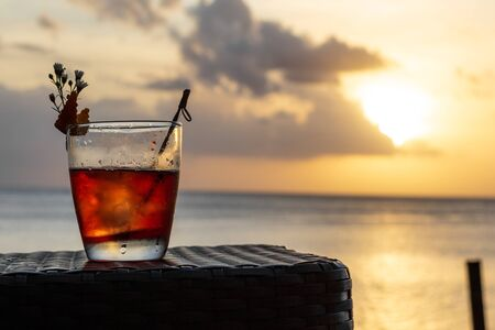 An iced summer cocktail isolated in front of a sunset over the sea Reklamní fotografie
