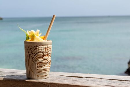 Summer tropical cocktails in a creative cup, with the sea behind Archivio Fotografico - 132725676