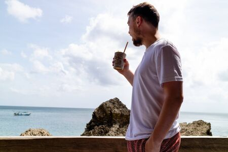 A young man drinking a tropical cocktail while looking at the sea Archivio Fotografico - 132580798
