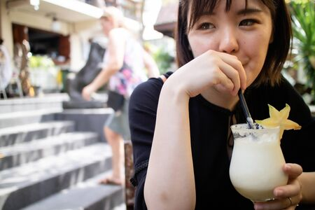 Beautiful young woman drinking a cocktail on holiday Archivio Fotografico - 132725774