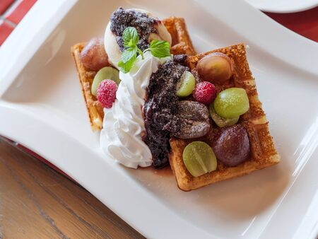 Delicious waffles with fresh fruits, ice cream and whipped cream on a white plate Archivio Fotografico - 132596293