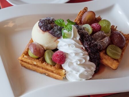Delicious waffles with fresh fruits, ice cream and whipped cream on a white plate Archivio Fotografico - 132596753
