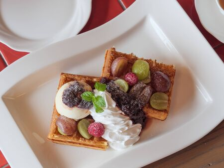 Delicious waffles with fresh fruits, ice cream and whipped cream on a white plate Archivio Fotografico - 132596170