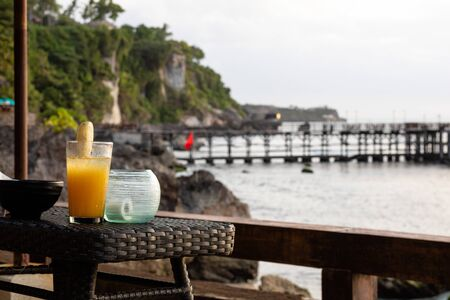 A tropical coktail waiting on a table with a sea view in the summer Archivio Fotografico - 133451832