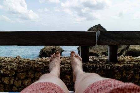 looking at a man's legs relaxing by the sea. Archivio Fotografico - 133664047