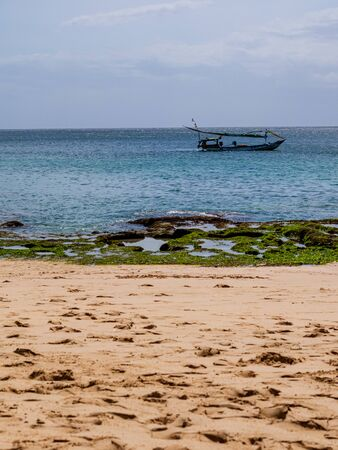 A scenic view of a beach and a boat floating in the background Archivio Fotografico - 134651277
