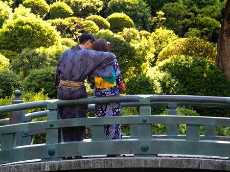A young couple wearing kimonos cuddling on a bridge.