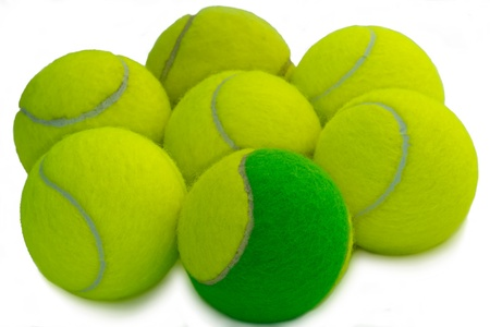 a different green tennis ball between yellow tennis balls on a white background photo