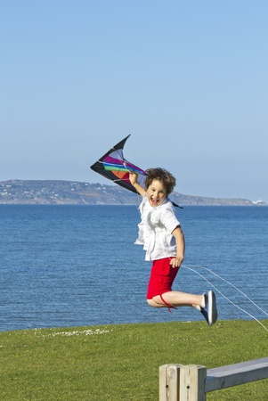 a happy boy jumping with a colorful kite photo