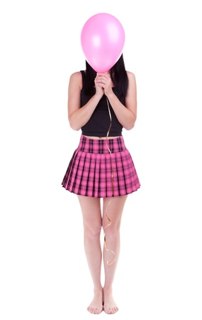 Young woman hiding her face behind pink balloon over white background  photo