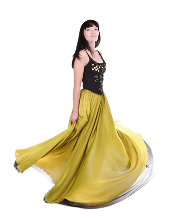 Beautiful woman twirling in her fashionable yellow-green colour dress