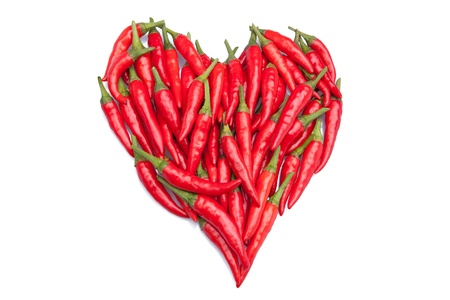 Red hot chili peppers in a heart shape on white background