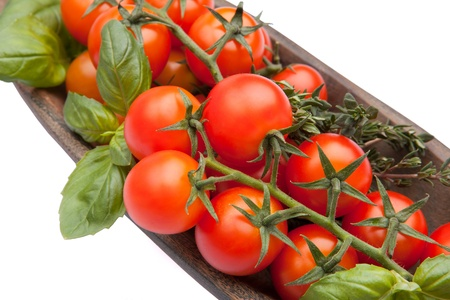 Cherry tomatoes with basil and thyme in wood plate isolated on white photo