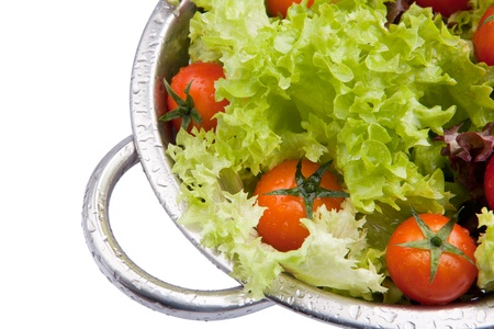 a colander: Washed fresh tomatoes with salad in colander Stock Photo
