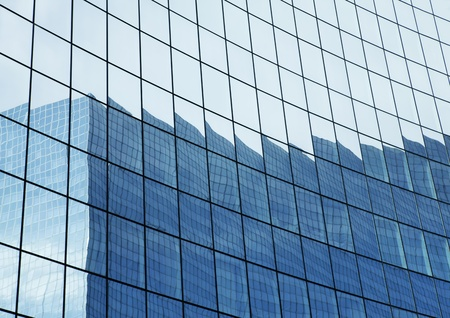 Reflection in glass wall of business building in another