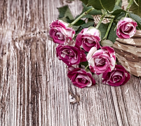 Mini roses  on vintage wooden surface photo