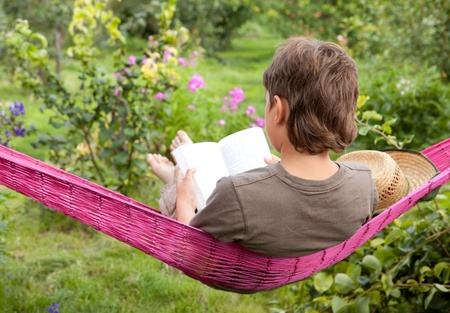 A child resting in  hammock and reading a book  in garden  photo