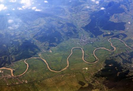 Een vogelperspectief van de grond met bochtige rivier met de stralen van de zon