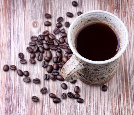 A vintage  cup with black coffee in   with roasted coffee beans on wooden surface photo