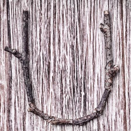 Latin capital alphabet letter U made from  sticks on vintage surface Stock Photo - 13549327