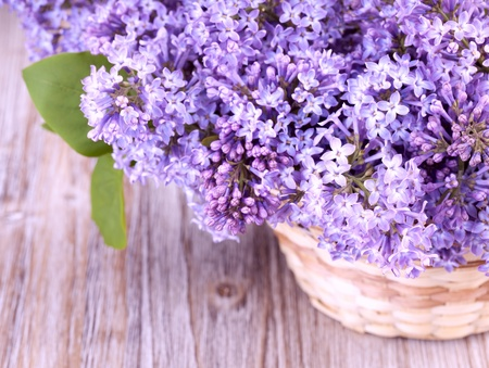 Beautiful lilac flowers in a basket on wooden vintage surface photo