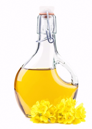 Extra virgin  oil in a bottle with rapeseed flowers isolated on white