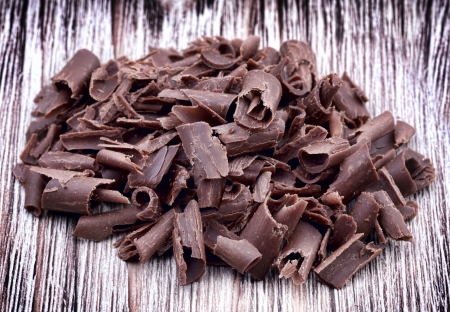 Curly pieces of milk chocolate on wooden vintage background photo