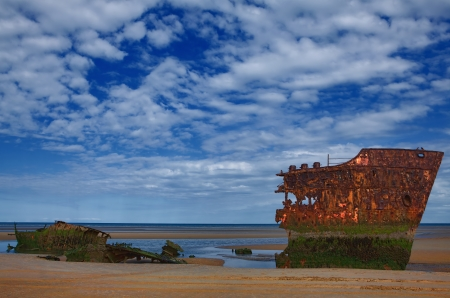 Leftovers of the old rusty ship on the coast of a ocean  photo
