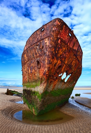 Deserted rusty ship on the coast of a ocean photo