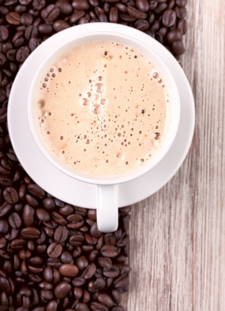 Cup of espresso with roasted coffee beans on wooden surface Stock Photo - 15564370