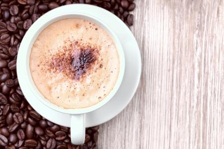 Espressotasse mit gerösteten Kaffeebohnen auf hölzernen vintage Oberfläche