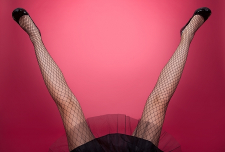 legs open: Sexy woman legs open wide on red blackground  Stock Photo