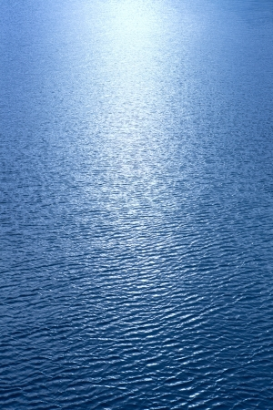 A beam of sunlight reflecting over rippled blue water photo