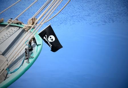 drapeau pirate: Un drapeau de pirate (Jolly Roger) sur voilier Banque d'images