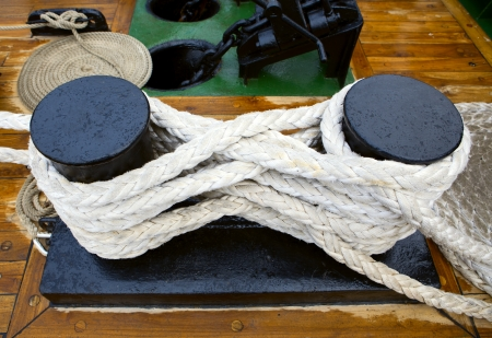 ship anchor: Bundle of rope on the black  bollard