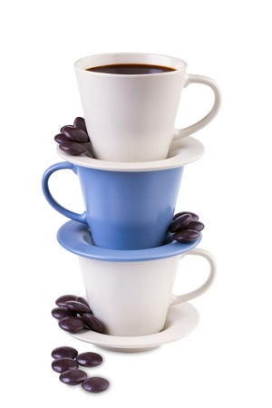 Three  coffee cups stacked together with little black chocolates isolated on white background Stock Photo - 16694007